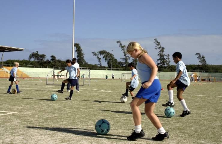 Bambini e bambine giocano a calcio